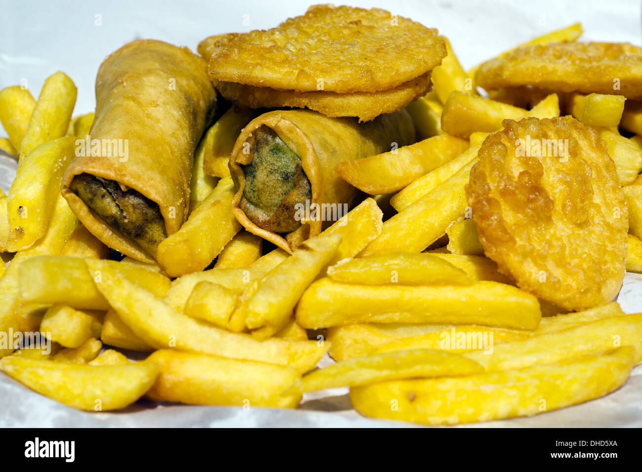 Chips potato, fritters and spring rolls fast food takeaway meal dish outdoor. - Stock Image