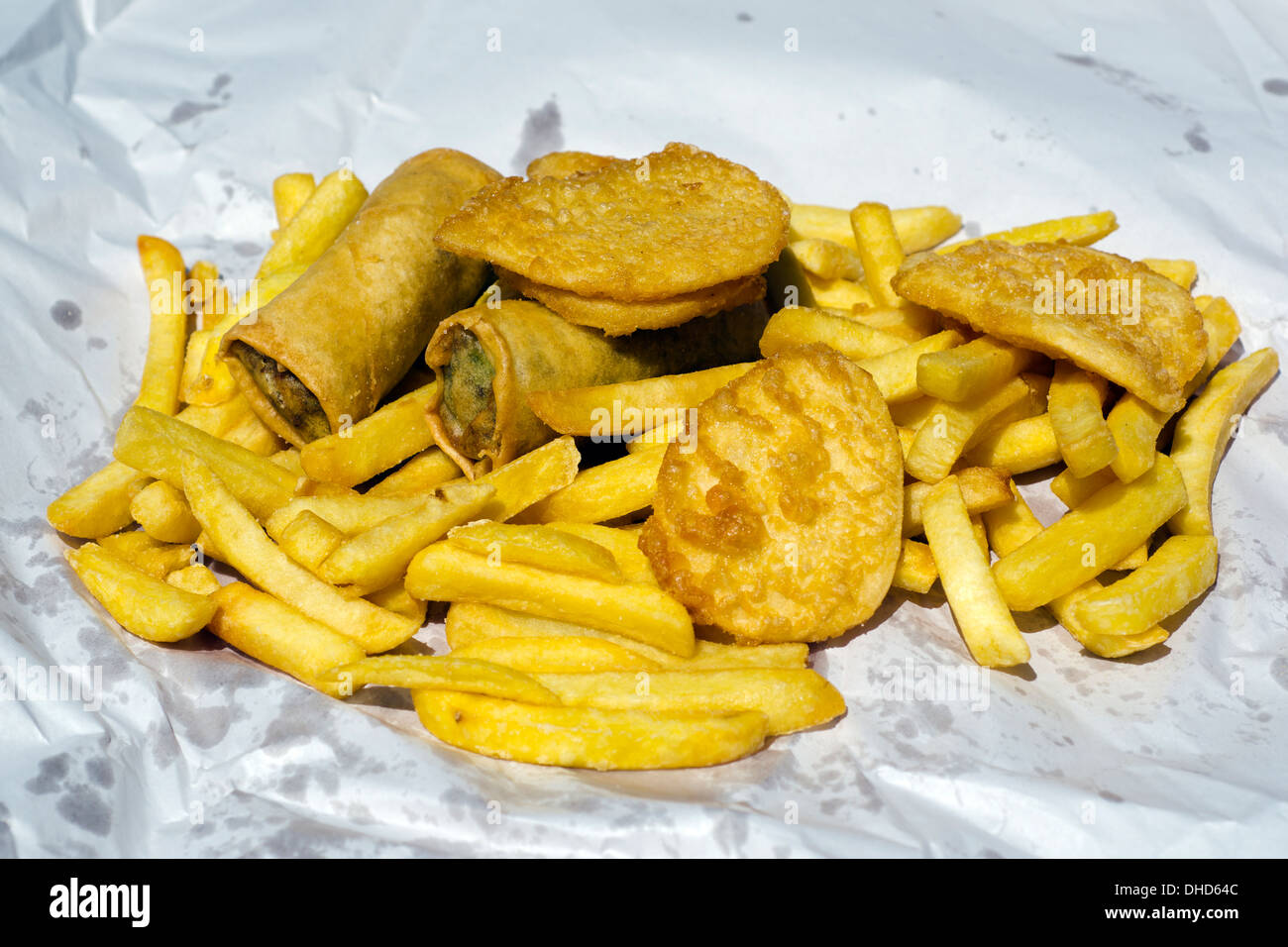 Chips potato, fritters and spring rolls fast food takeaway meal dish outdoor. Stock Photo