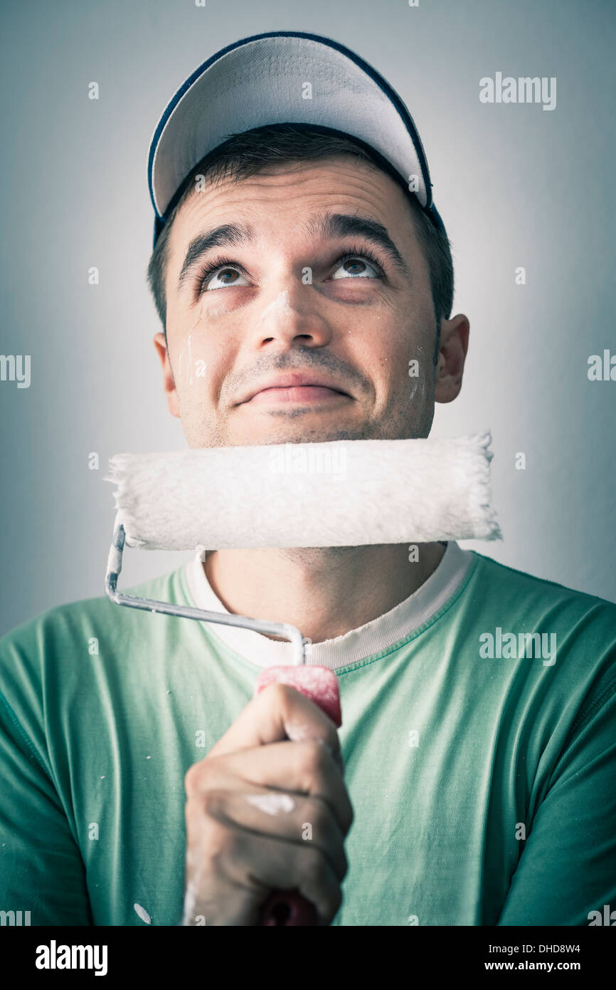 Thoughtful smiling creative man with paint roller looking up. - Stock Image