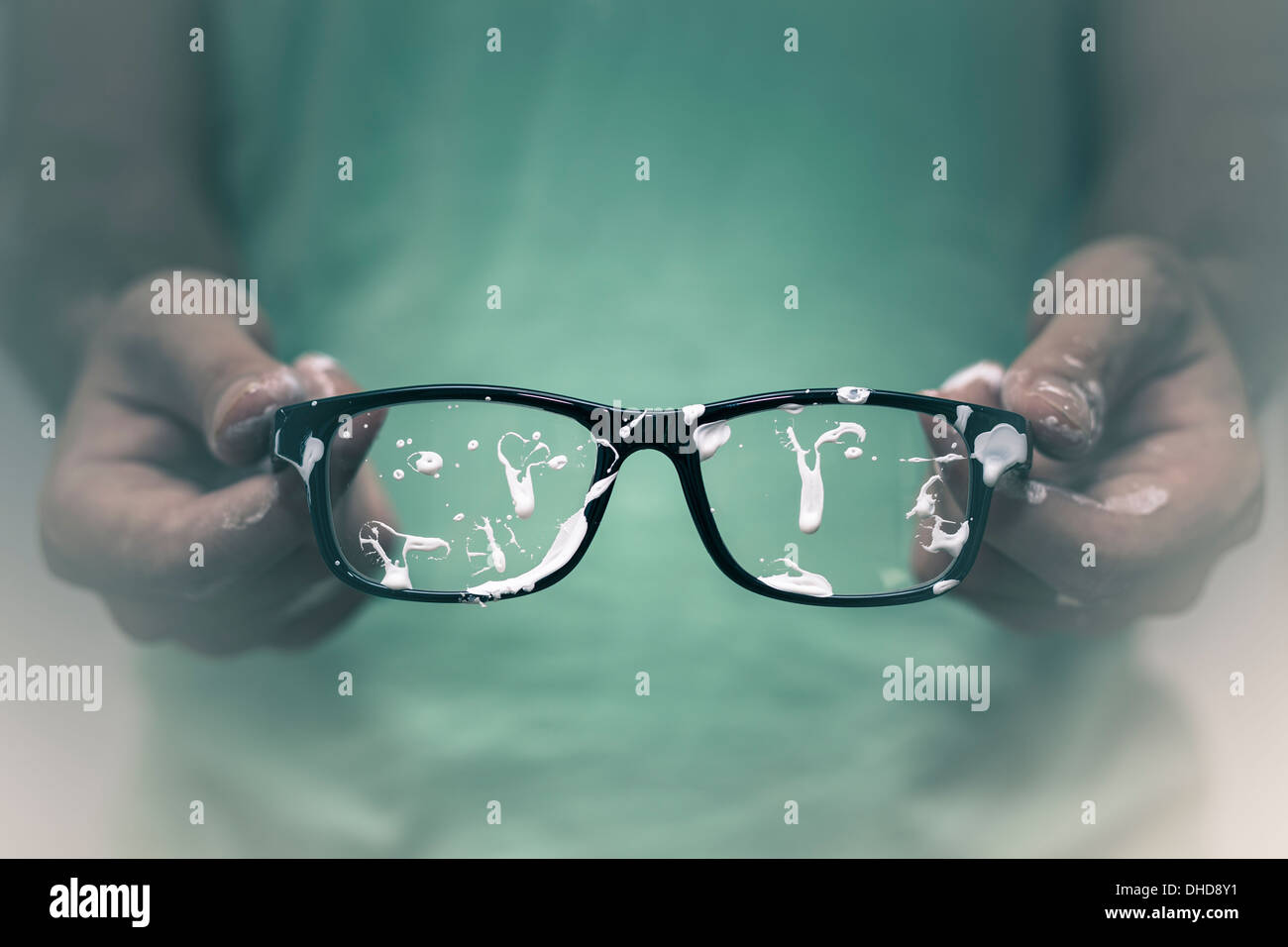 Creative vision concept. Closeup of creative man showing his stained eyeglasses. - Stock Image
