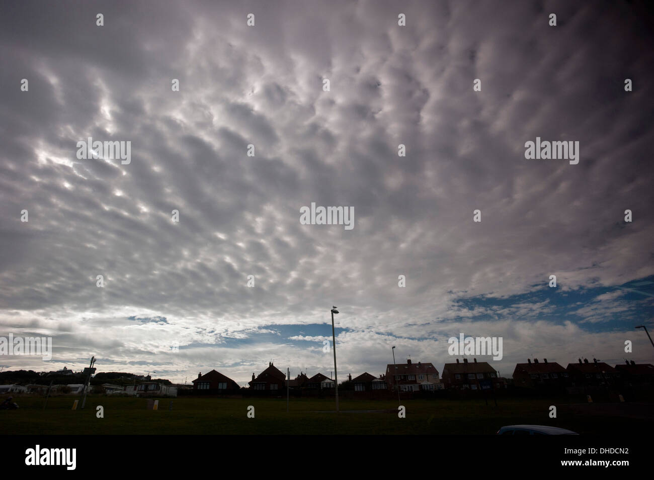 An Asperatus formation cloudbank of Stratocumulus clouds loom over suburban houses on the seafront at South Shields, Tyne and Wear. - Stock Image
