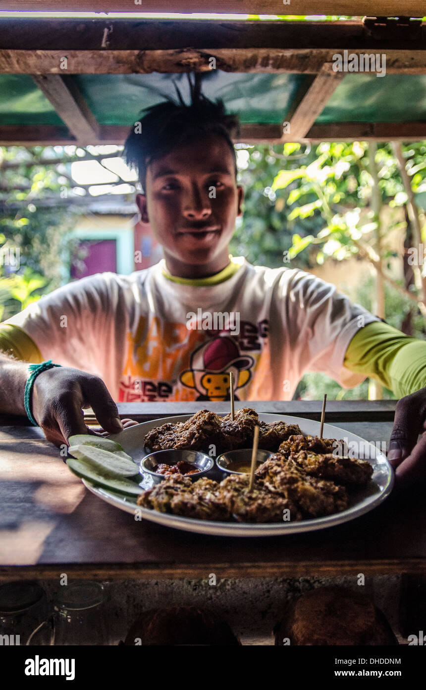 A waiter prepares to serve pakoras, Pokhara, Nepal, Asia - Stock Image