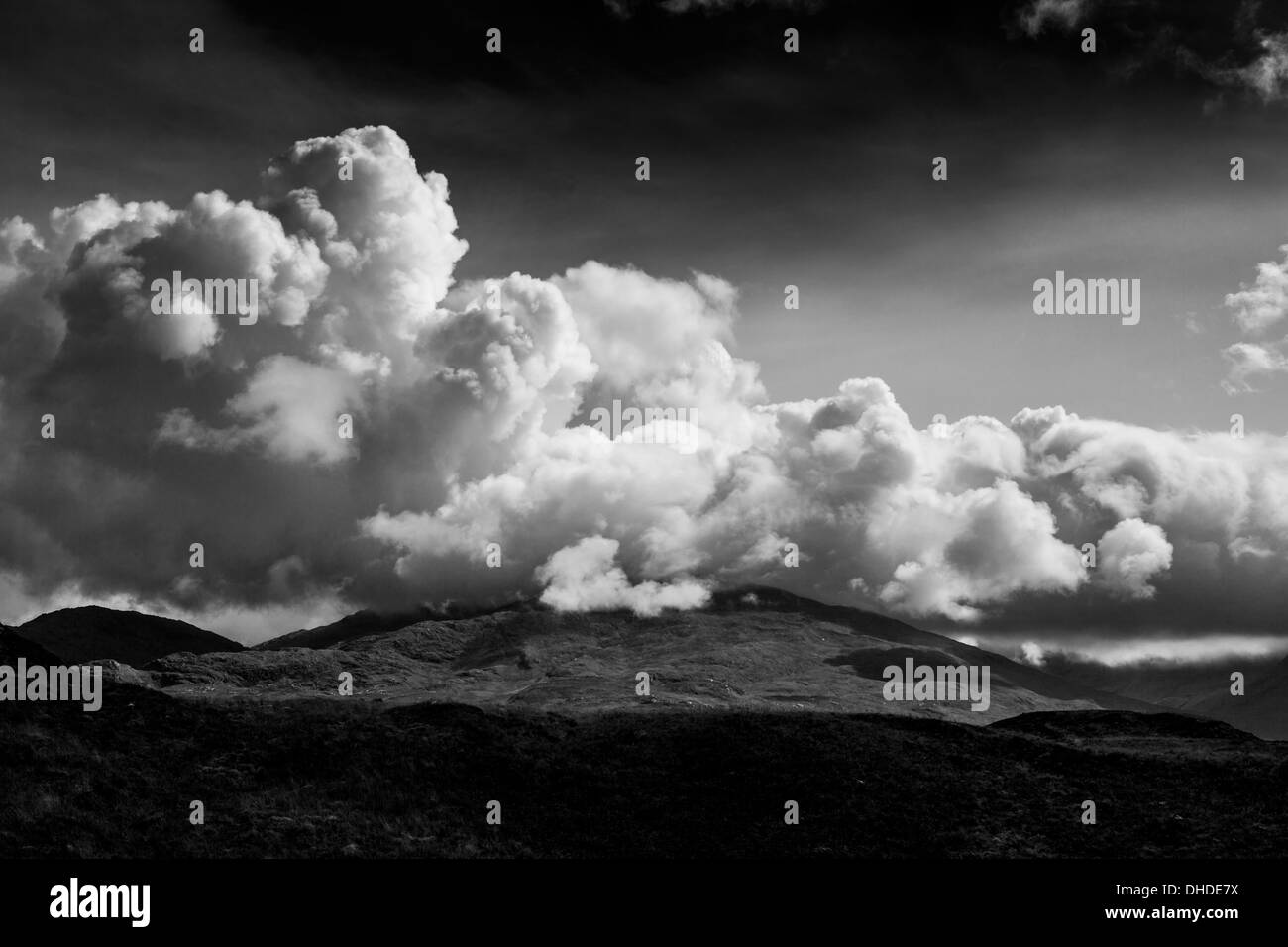 Impressive cumulonimbus clouds roll over the top of a hill - Stock Image