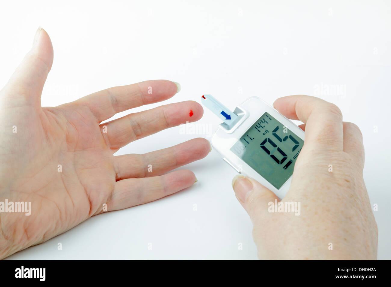 Diabetic blood glucose test - blood on finger tip and meter strip - Stock Image
