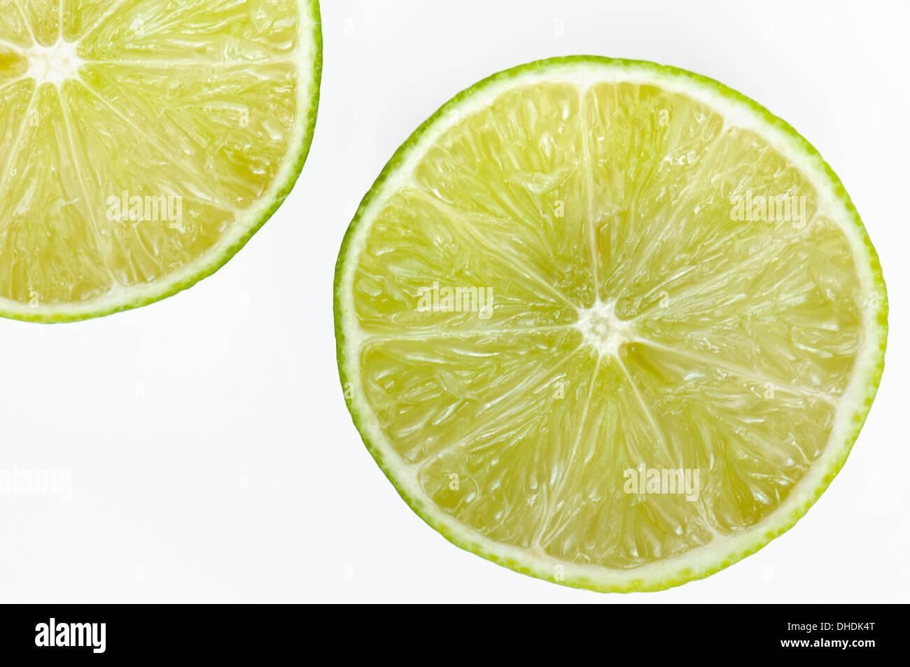 Halved lime segments on white background - Stock Image