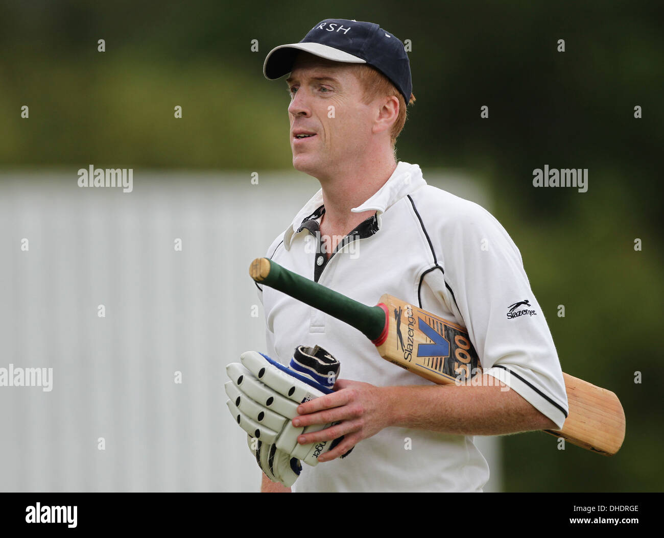 Actor Damian Lewis walks off the cricket field with his cricket gloves and his bat tucked under his arm. - Stock Image