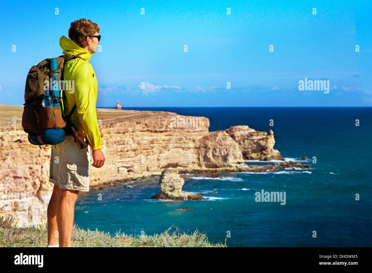 Man Traveler with backpack relaxing outdoor with Sea and Rocks coastal on background Freedom and Healthy Lifestyle concept - Stock Image
