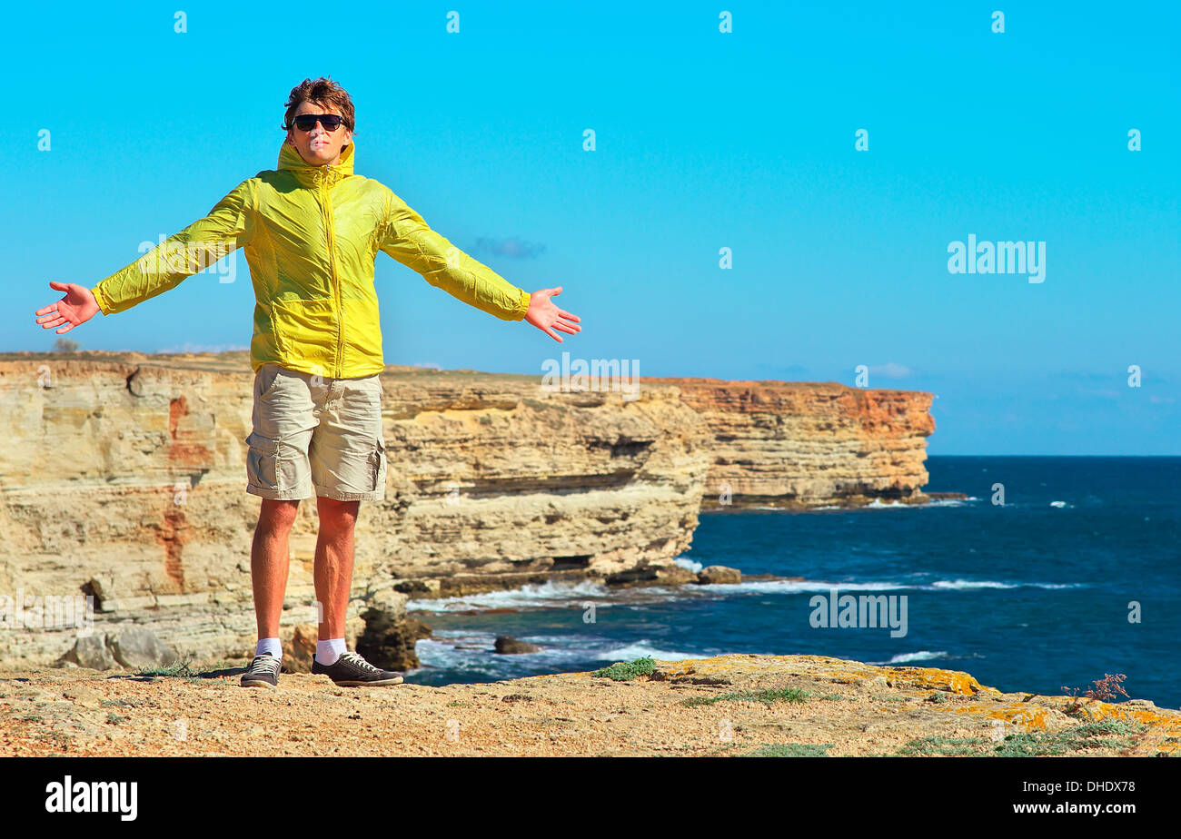 Man Traveler standing outdoor hands raised to the blue sky with Sea and Rocks coastal on background Freedom and Healthy Lifestyl - Stock Image