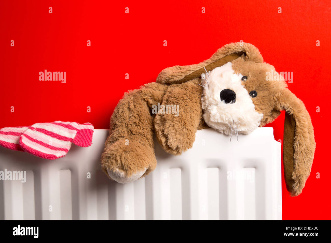 A child's bedroom with a teddy bear and a pair of mittens placed on top of a radiator heater. - Stock Image