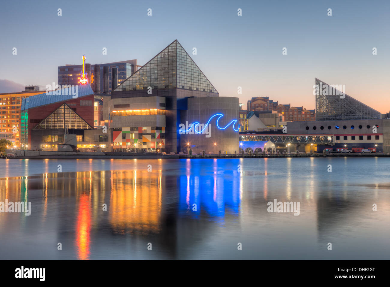 The Baltimore National Aquarium reflects off the waters of the Inner Harbor before sunrise in Baltimore, Maryland. - Stock Image