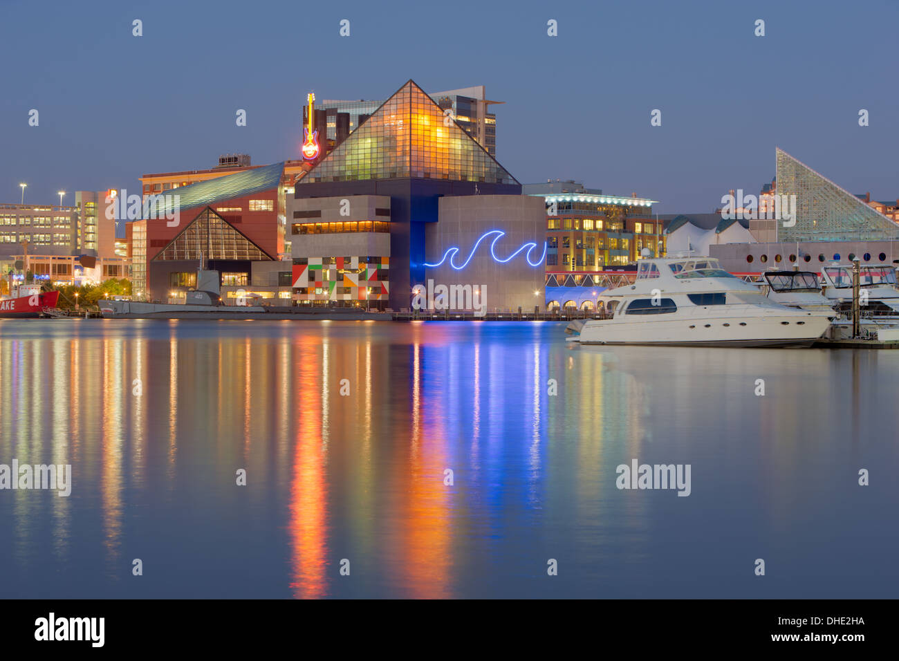 Lights from the National Aquarium reflect off the waters of the Inner Harbor during evening twilight in Baltimore, Maryland. - Stock Image