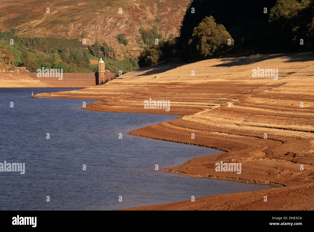 A fisherman stands on the edge of PenyGarreg Reservoir, Elan Valley during a severe drought. Stock Photo