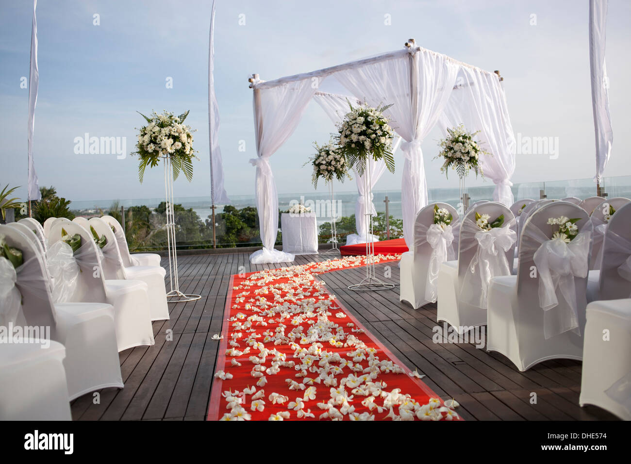 wedding venue setup corridor red flowers decor  decoration decorative sunset white cloth square structure ceremony carpet - Stock Image