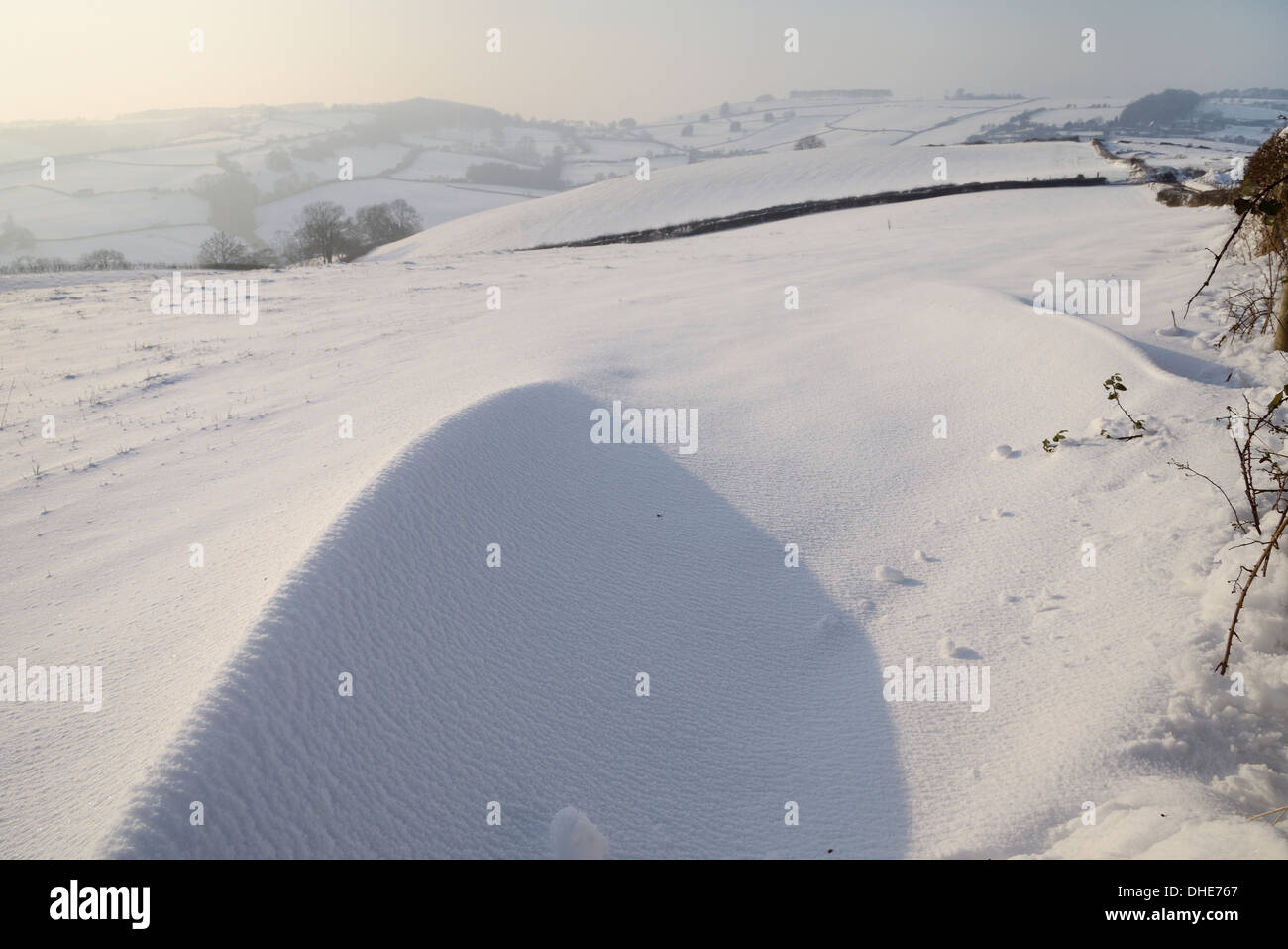 Snow drift on exposed hillside pastureland in late afternoon light, Tadwick, Bath and Northeast Somerset, UK, January. - Stock Image