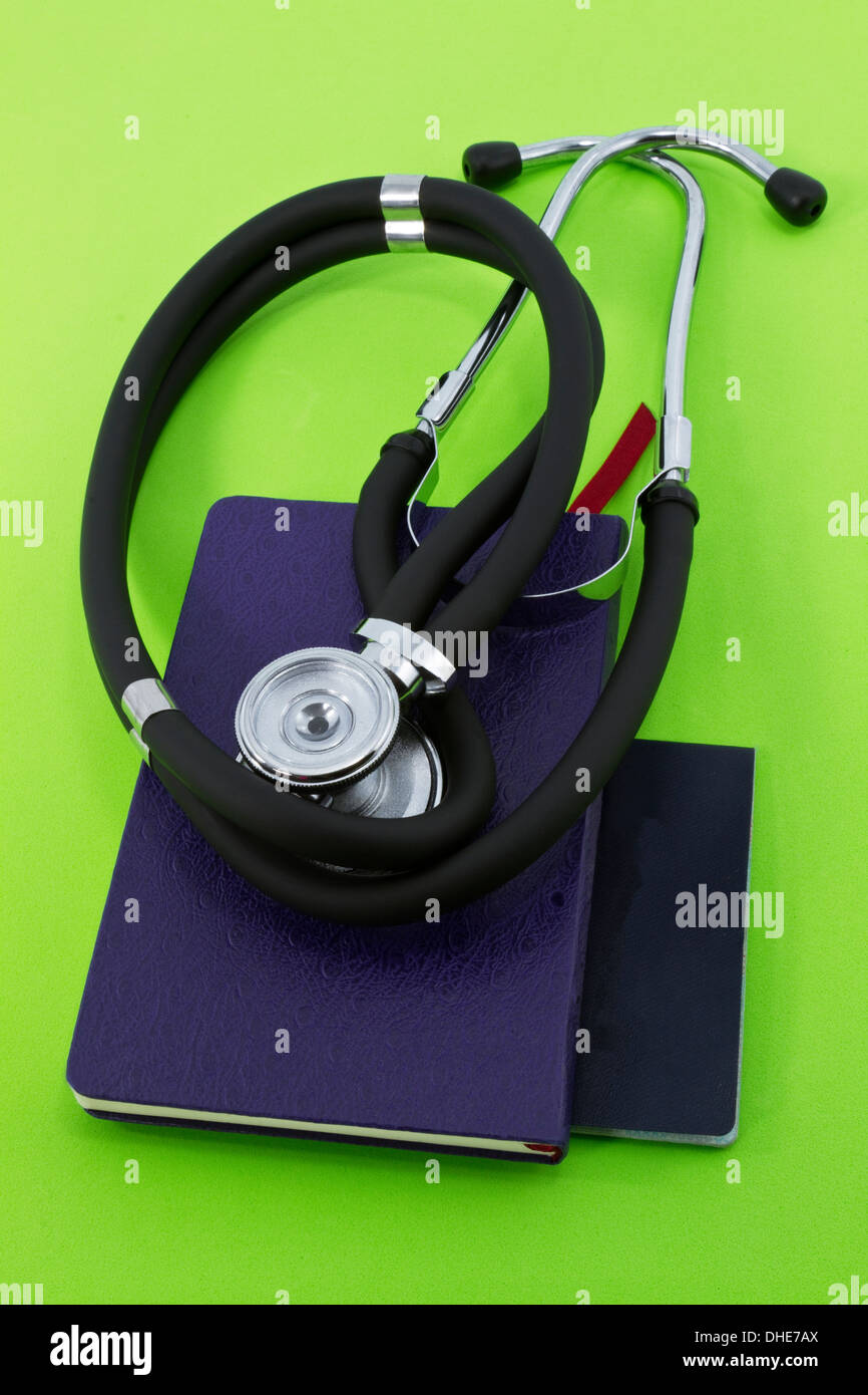 Stethoscope placed on small notebooks against fresh, green background suggestive of new policy, ideas, and concepts on medicine. - Stock Image