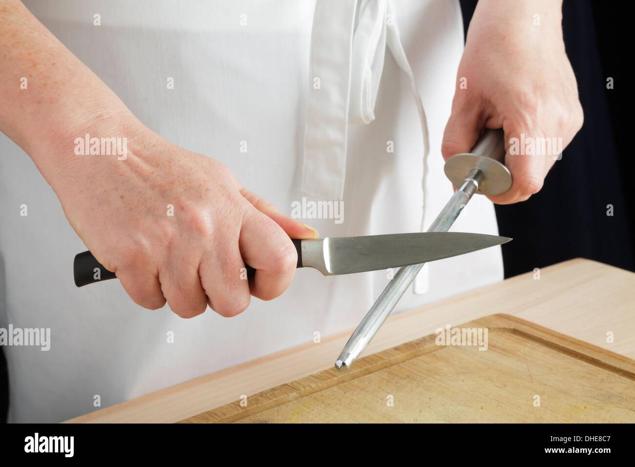 Using a kitchen knife sharpener - Stock Image