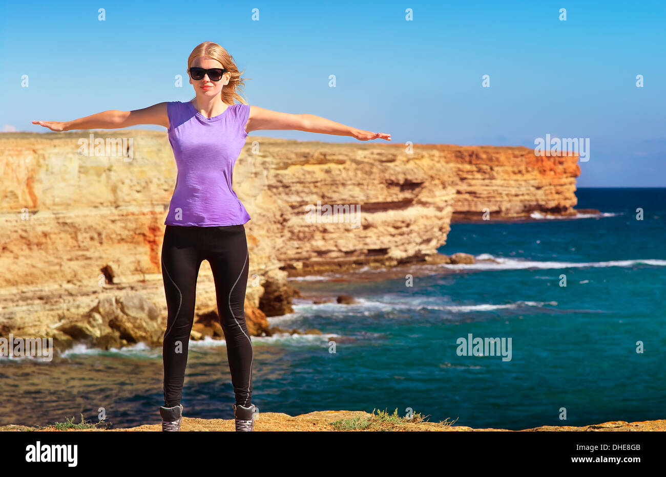 Woman Traveler standing outdoor hands raised to the blue sky with Sea and Rocks coastal on background Freedom Lifestyle - Stock Image