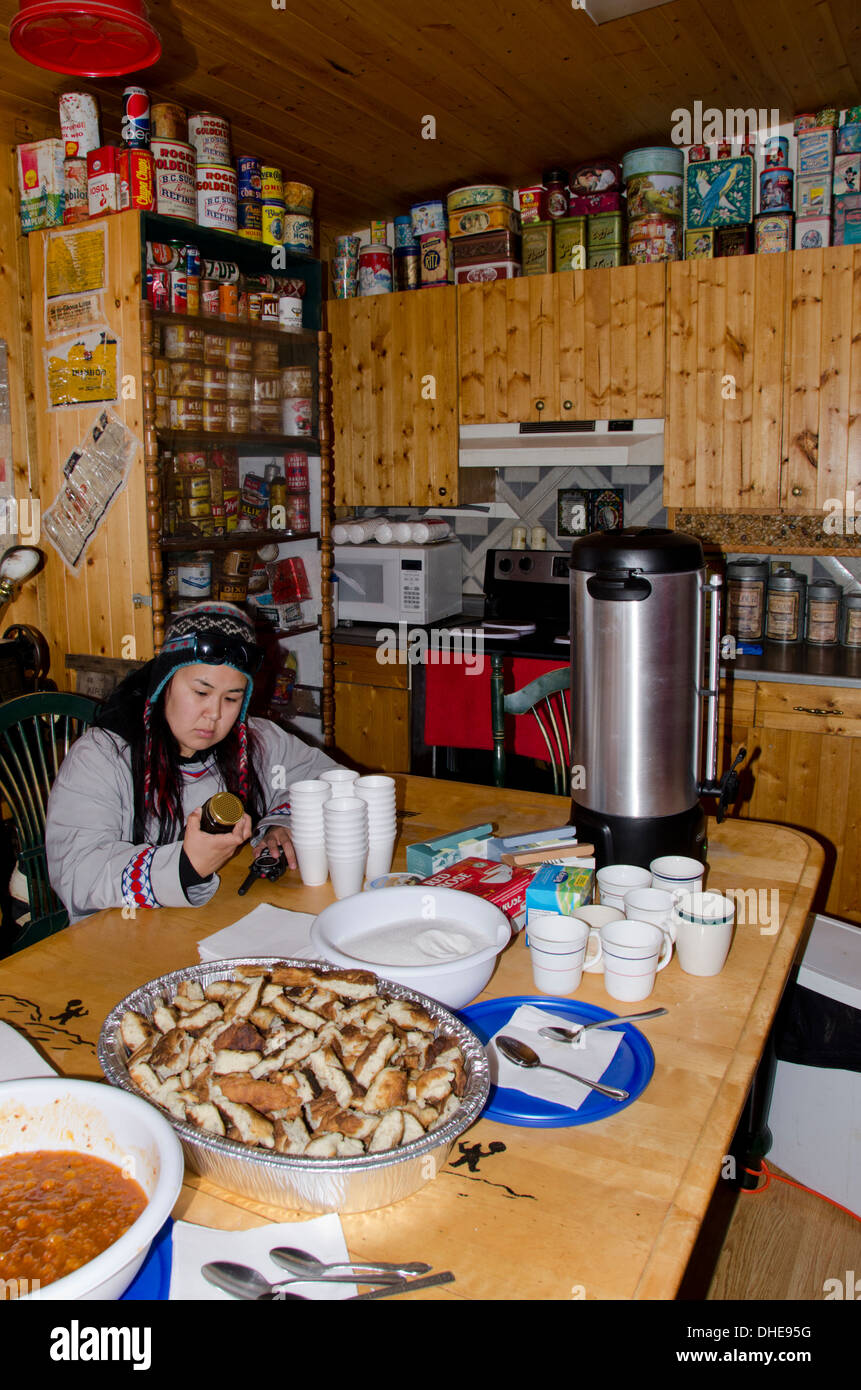 Canada, Nunavut, western shore of Hudson Bay, Kivalliq Region, Arviat. Inside typical arctic home, Inuit girl in kitchen. - Stock Image