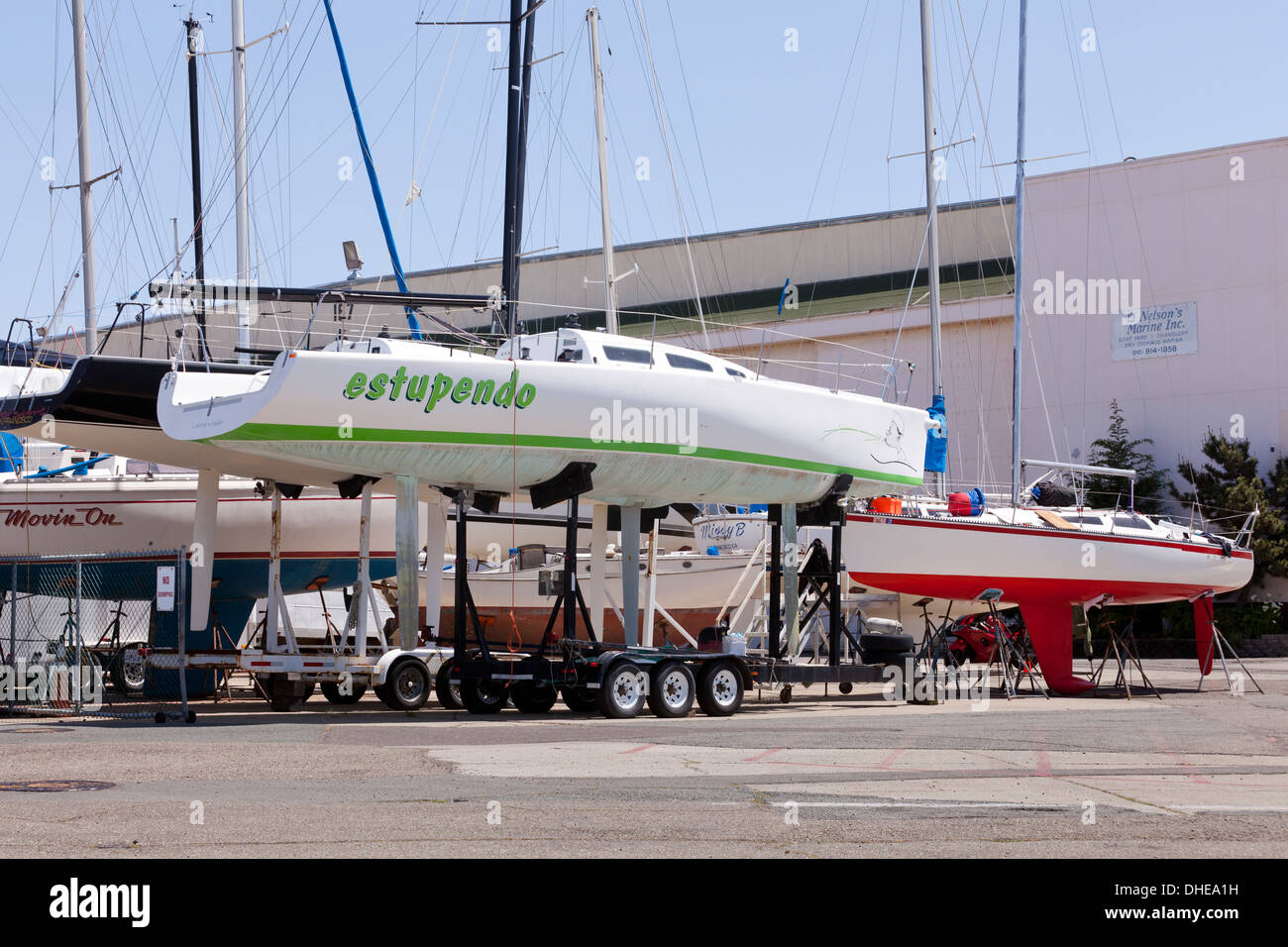 Sail boats on stands at boatyard - Alameda, California USA - Stock Image