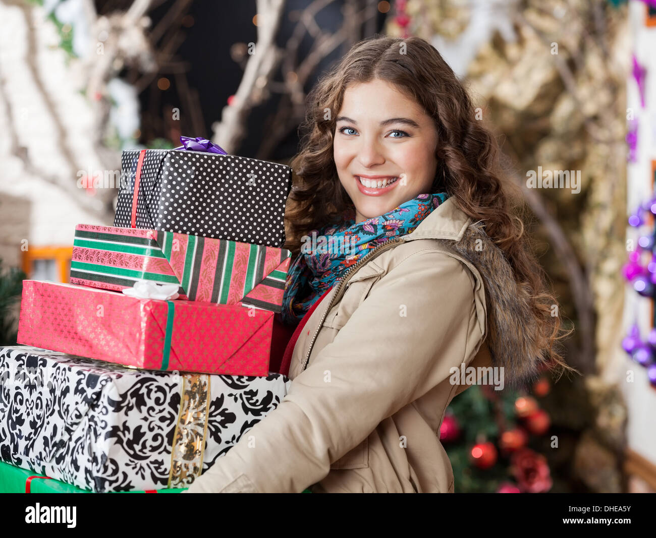 Woman Carrying Stacked Christmas Gifts In Store - Stock Image