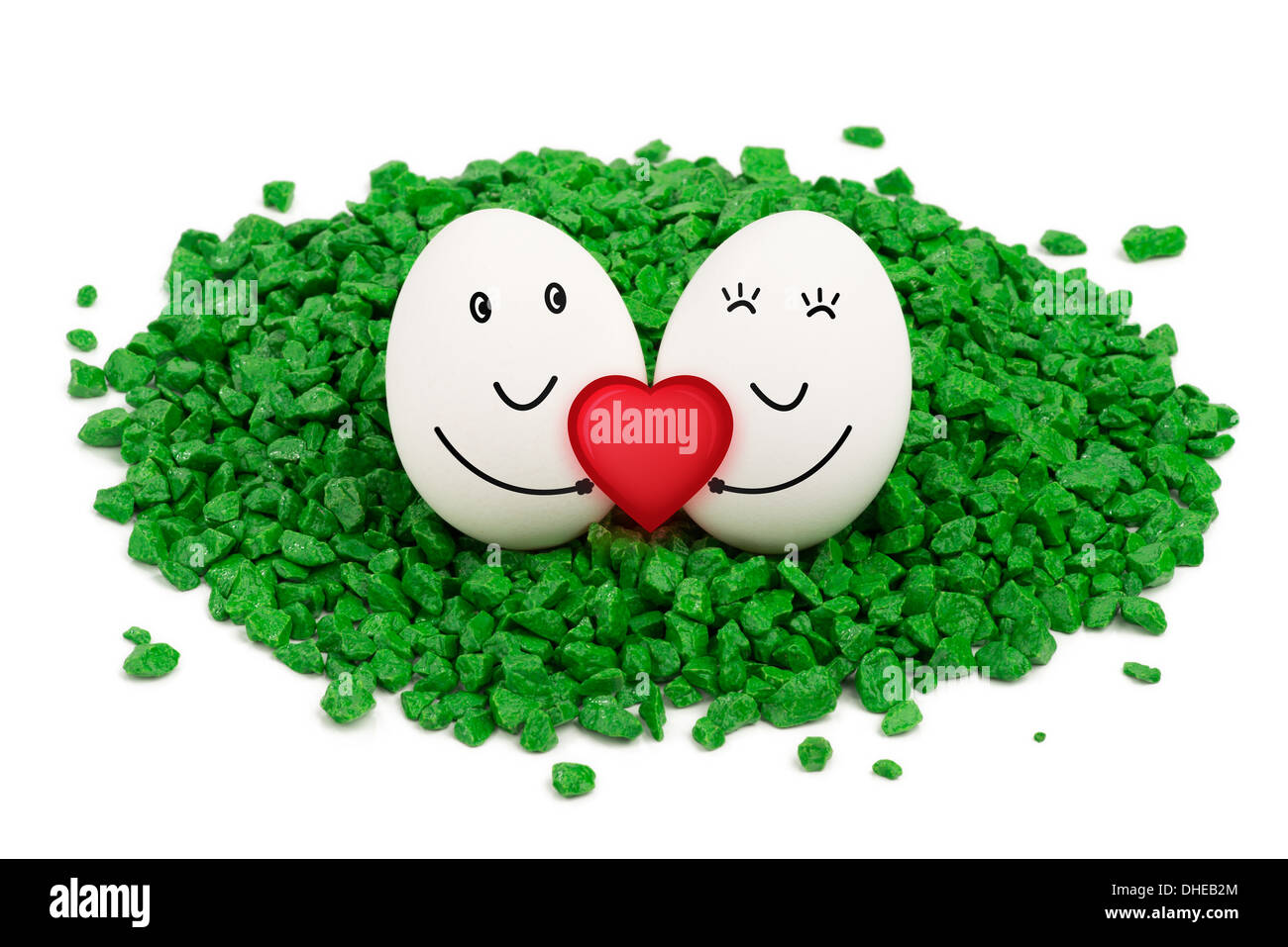 Two eggs lie on a green stones, are smiling and holding a red heart. - Stock Image