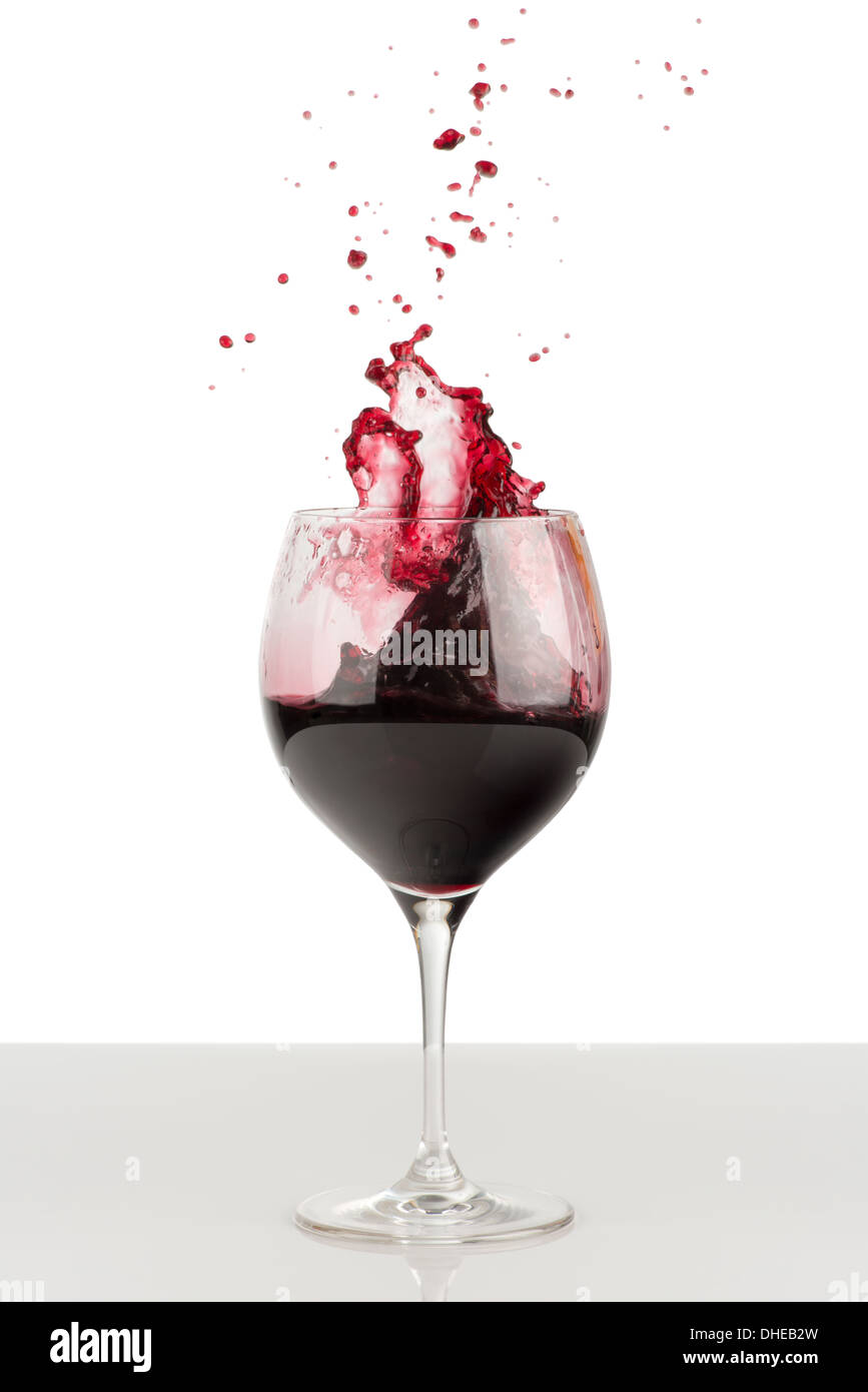 Splash of red wine in glass. Nearby there are splatter of wine. A glass stands on a glossy gray surface and isolated on white - Stock Image