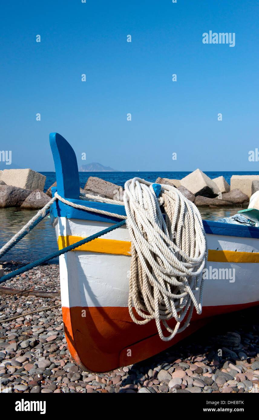 Fishing boat on the rocky beach at Lingua, Salina, The Aeolian Islands, off Sicily, Messina Province, Italy, Mediterranean - Stock Image