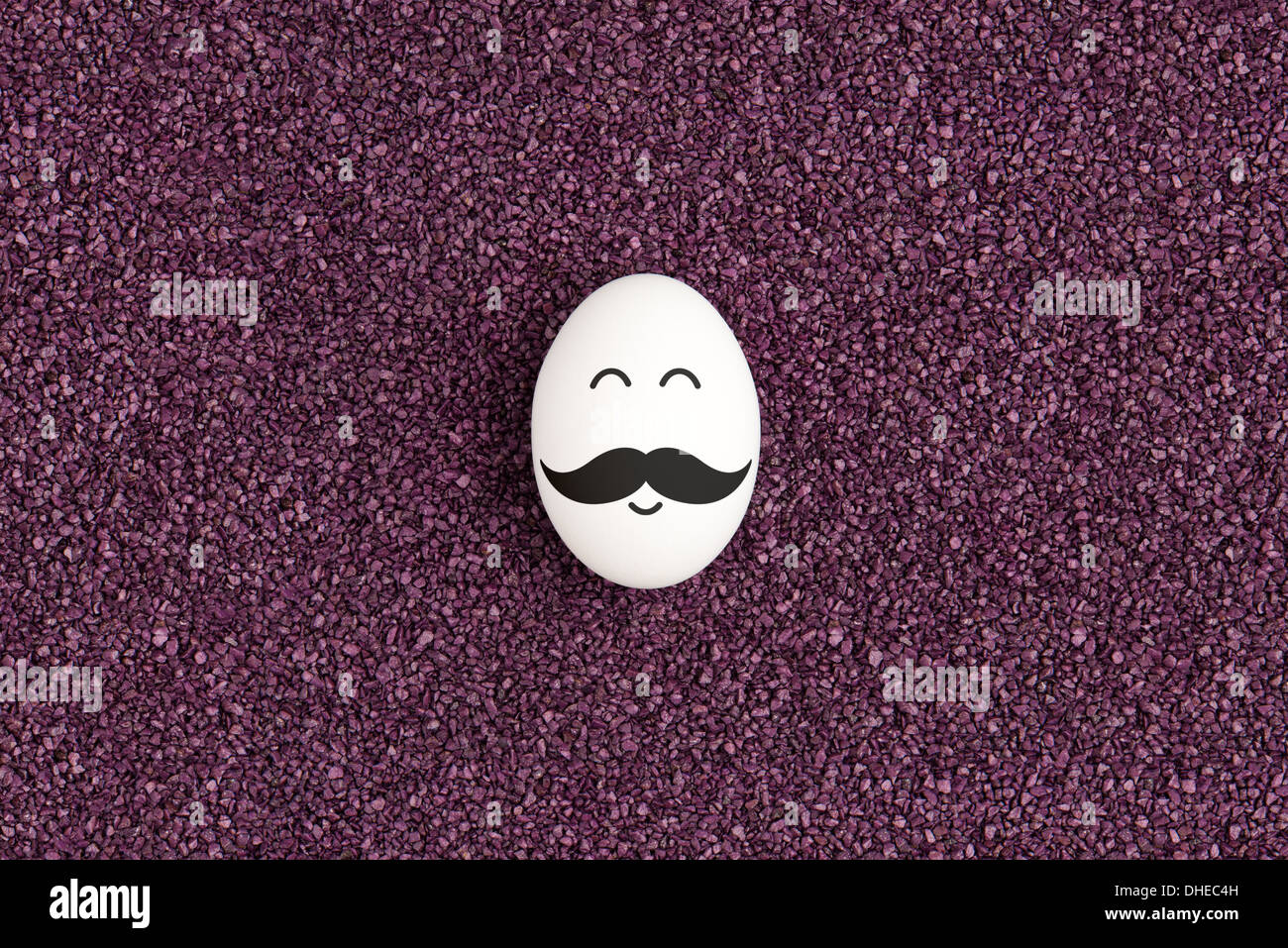 A Single Egg With Mustache Are Lying On The Decorative Purple Sand