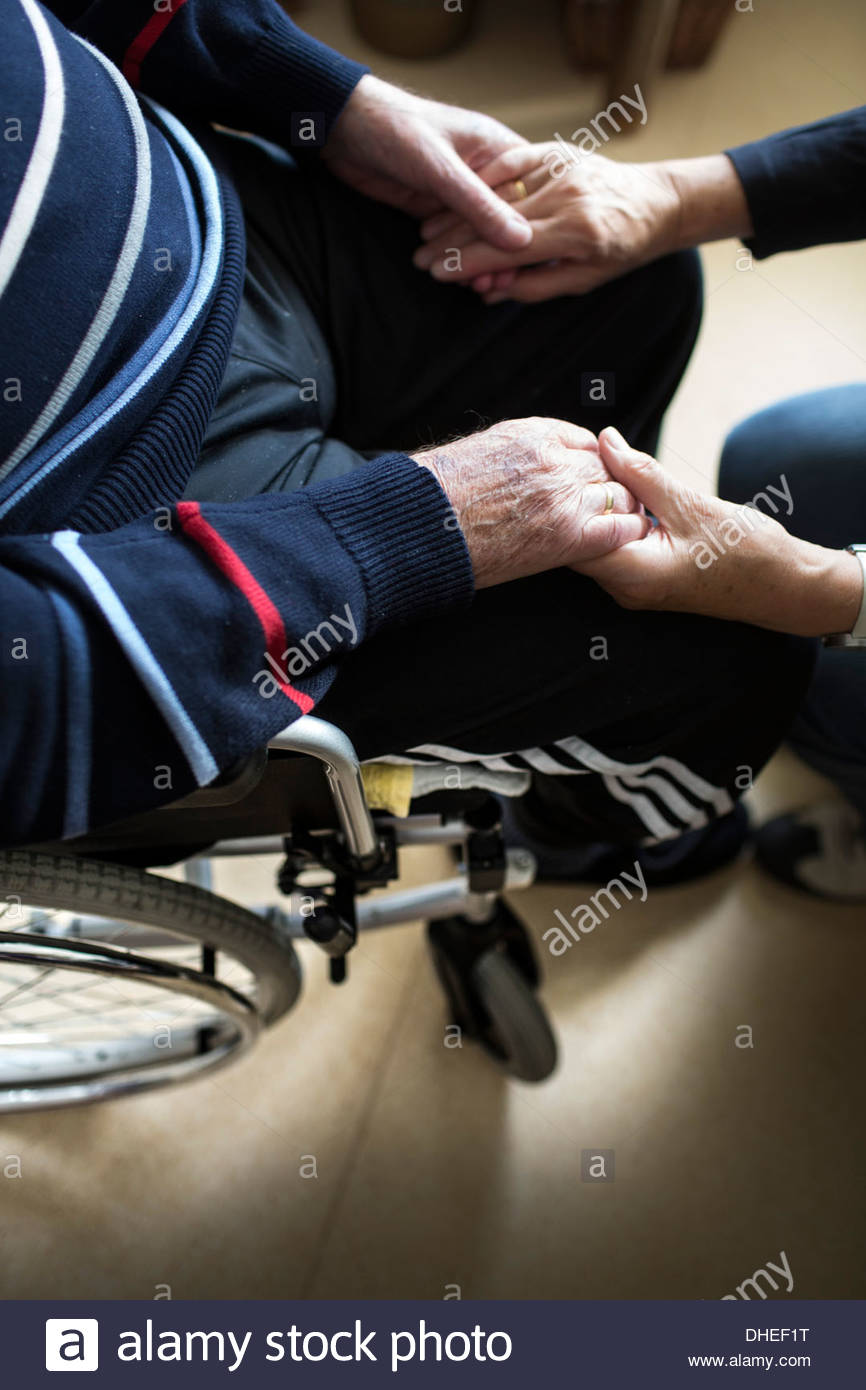Senior woman holding hands of her ill husband in a nursing home - Stock Image