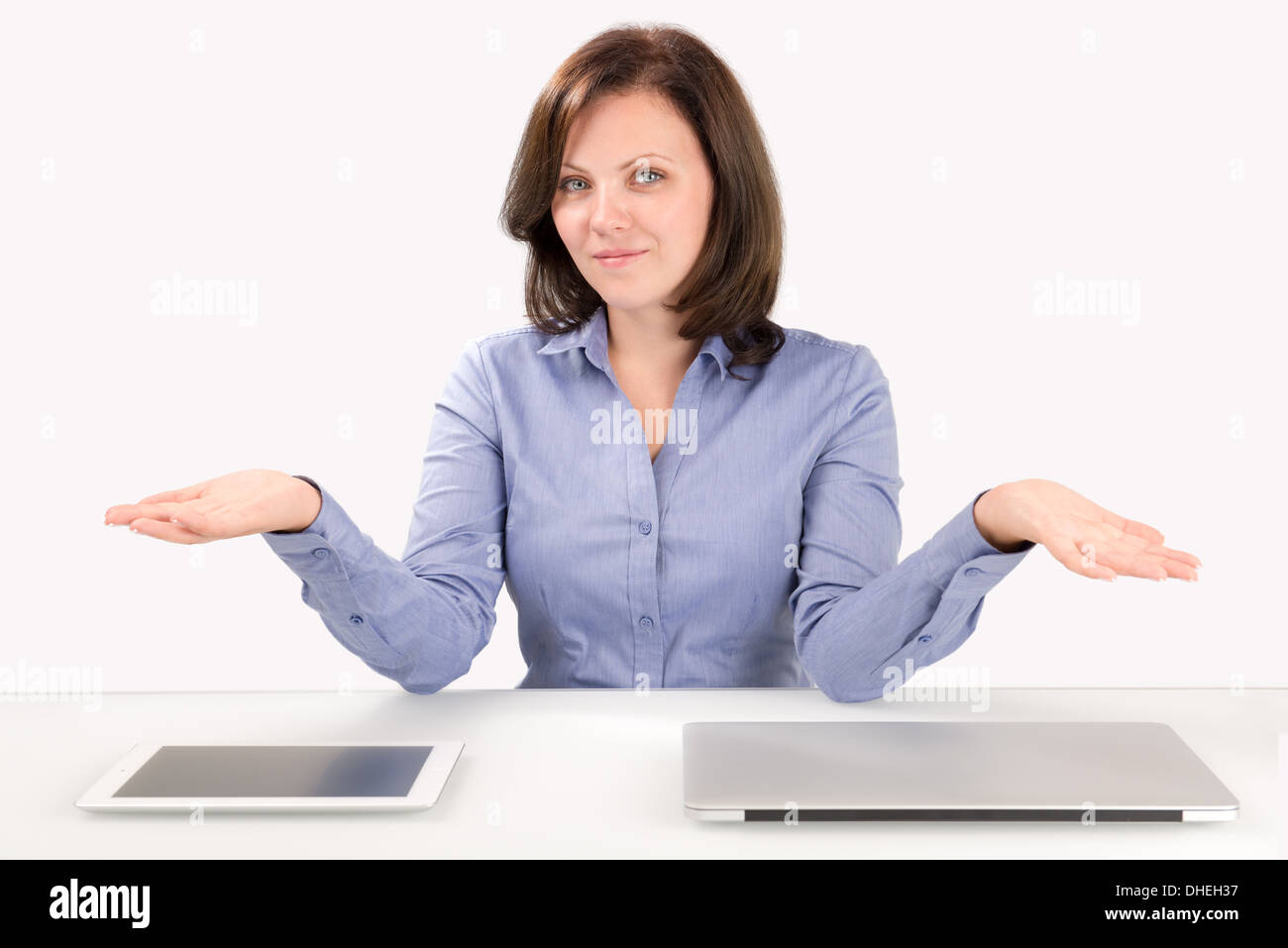 Business woman offers to make a choice between a tablet computer and a laptop, business concept - Stock Image