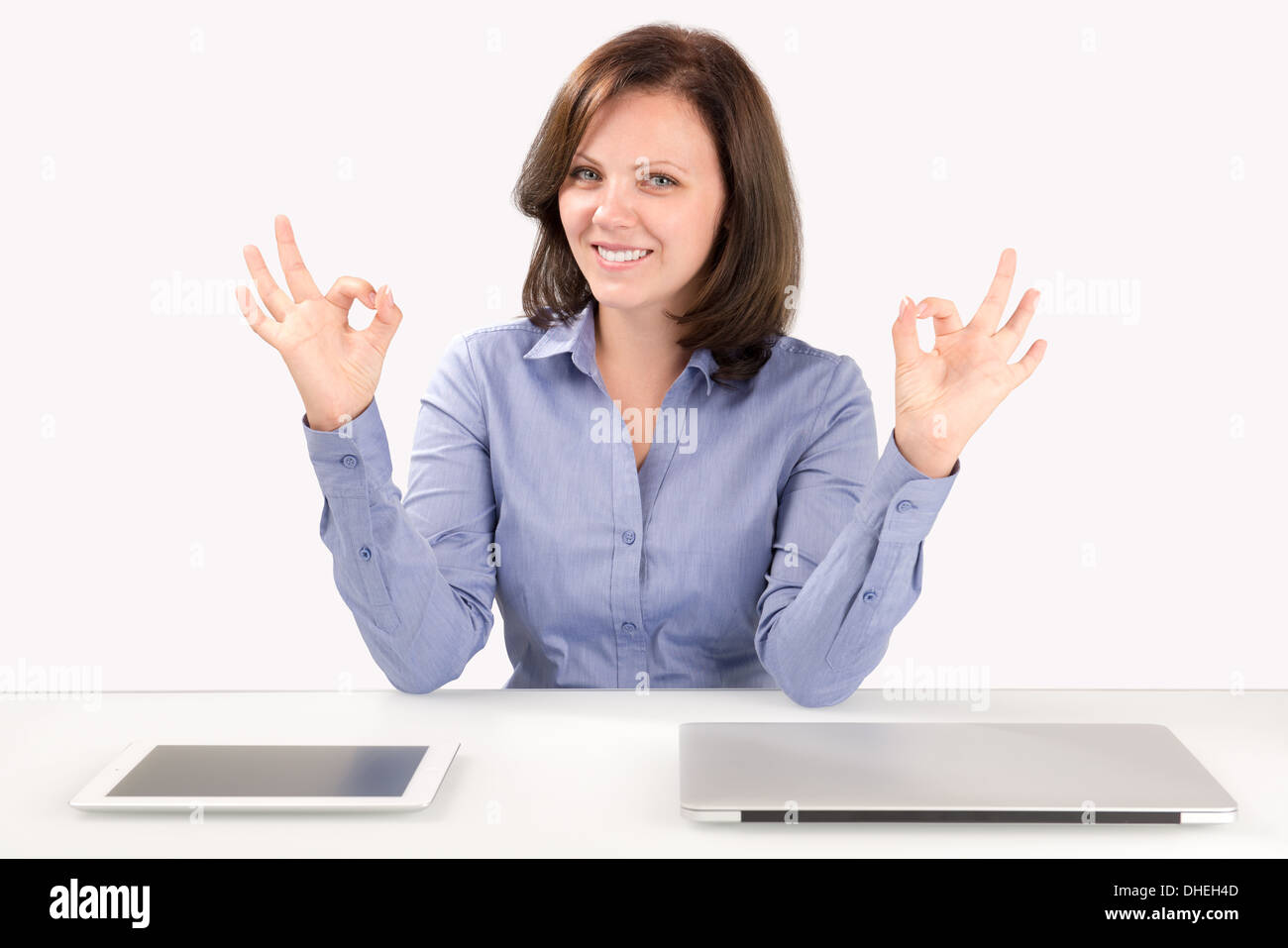 Business woman is sitting in front of a laptop and a tablet computer and showing double ok gesture - Stock Image