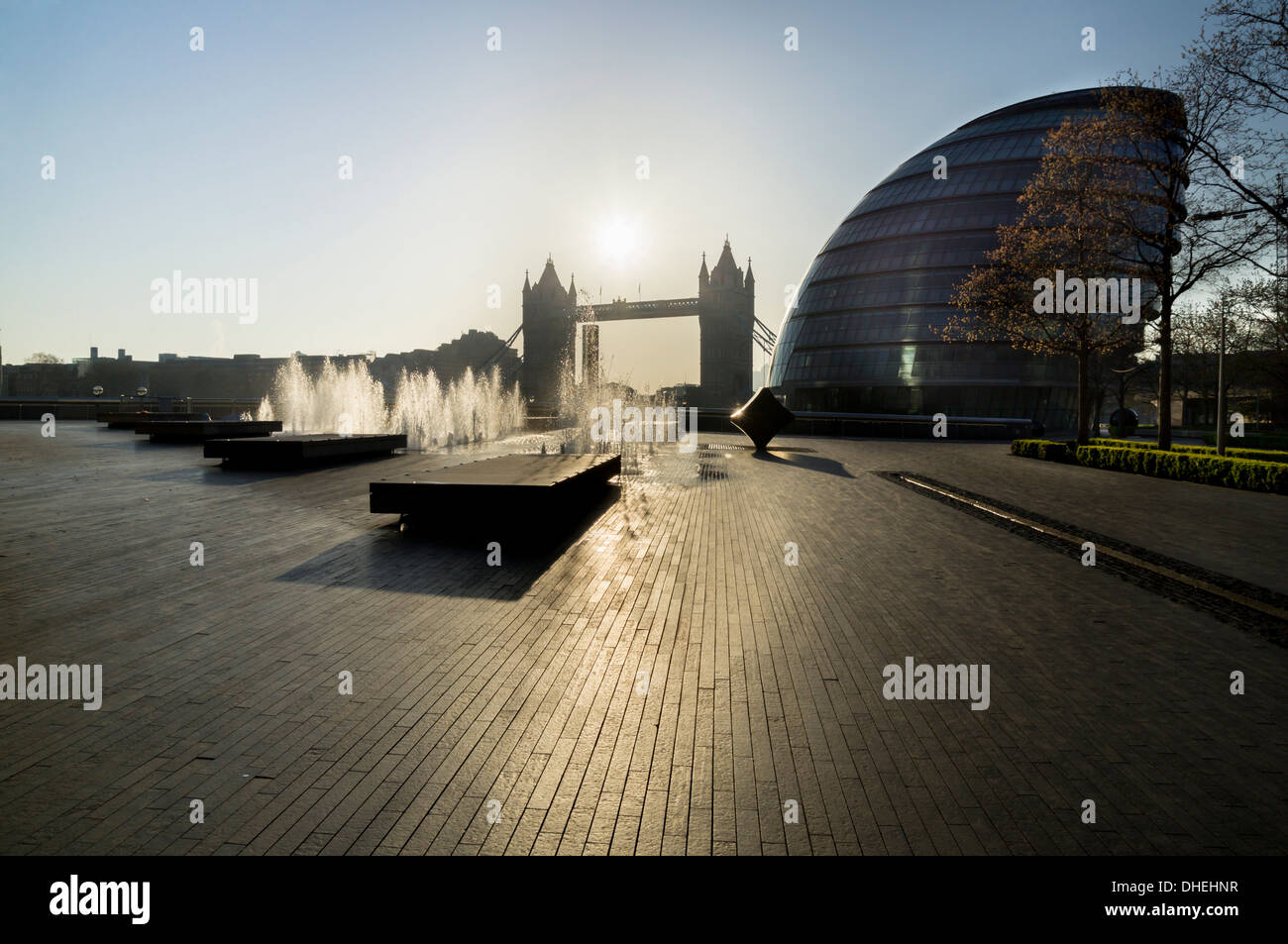 Fountains glisten at More Place with City Hall and Tower Bridge behind, London, England, United Kingdom, Europe - Stock Image