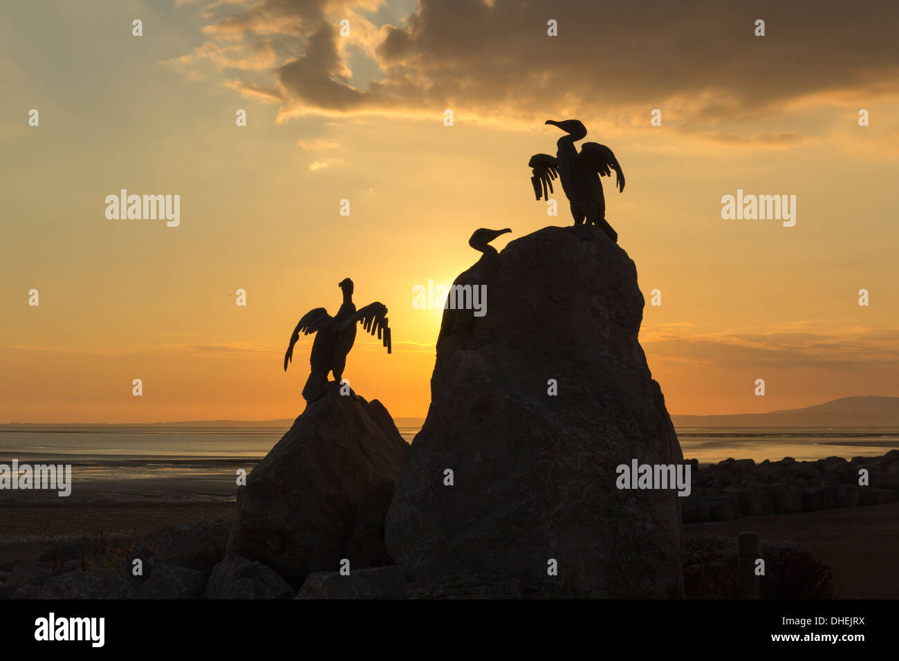 Cormorant statues on the seafront in Morecambe, Lancashire, silhouetted by the setting sun, part of the artwork 'Tern Project'. - Stock Image