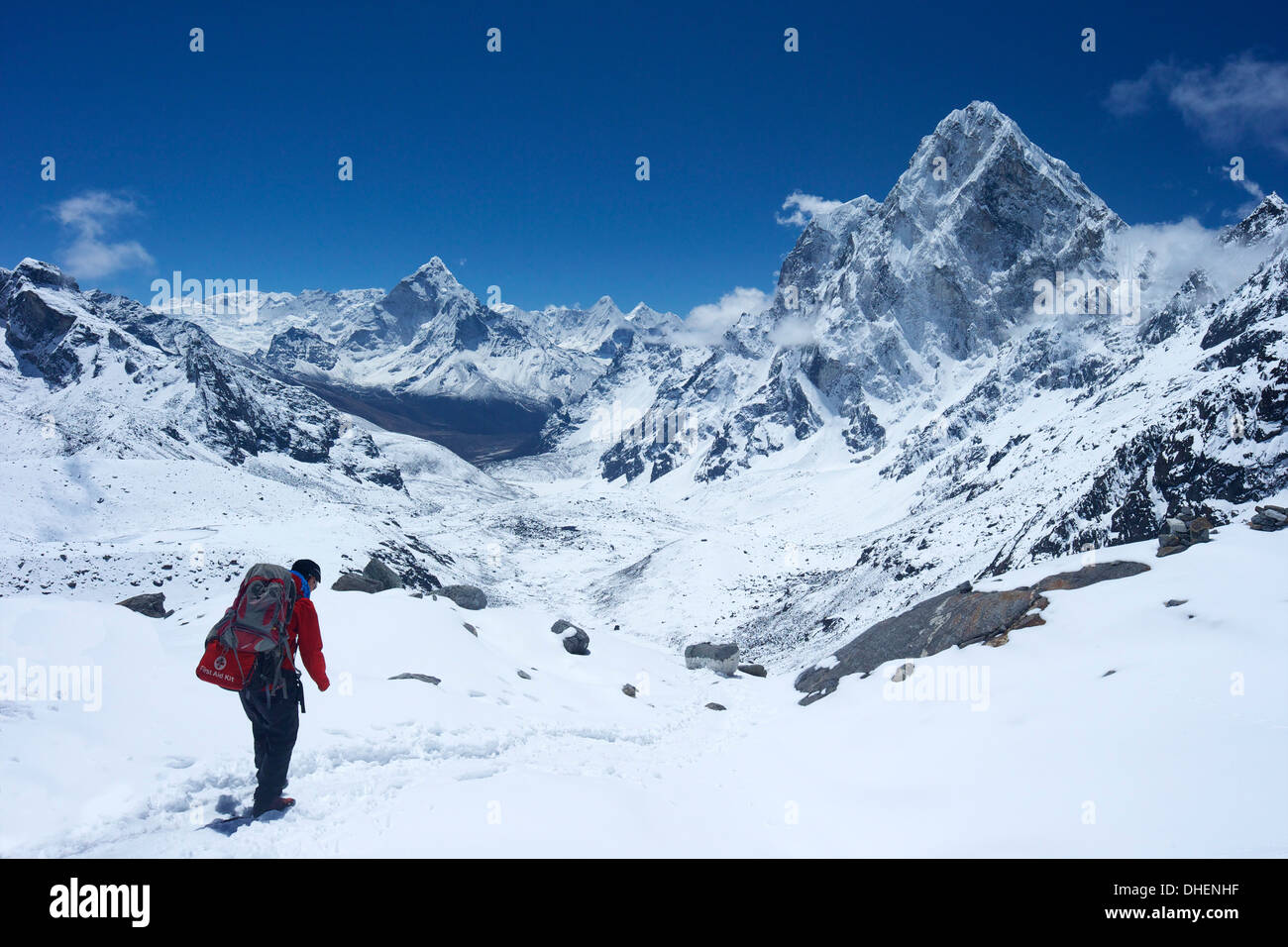 Sherpa guide walking over Cho La Pass with Ama Dablam on left and Arakam Tse on right side, Nepal, Himalayas - Stock Image