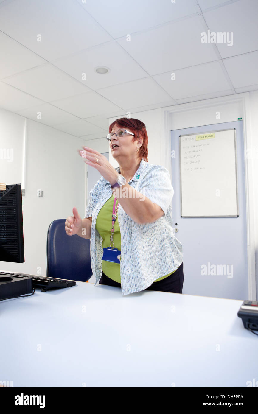 A female receptionist at an outpatient clinic UK - Stock Image