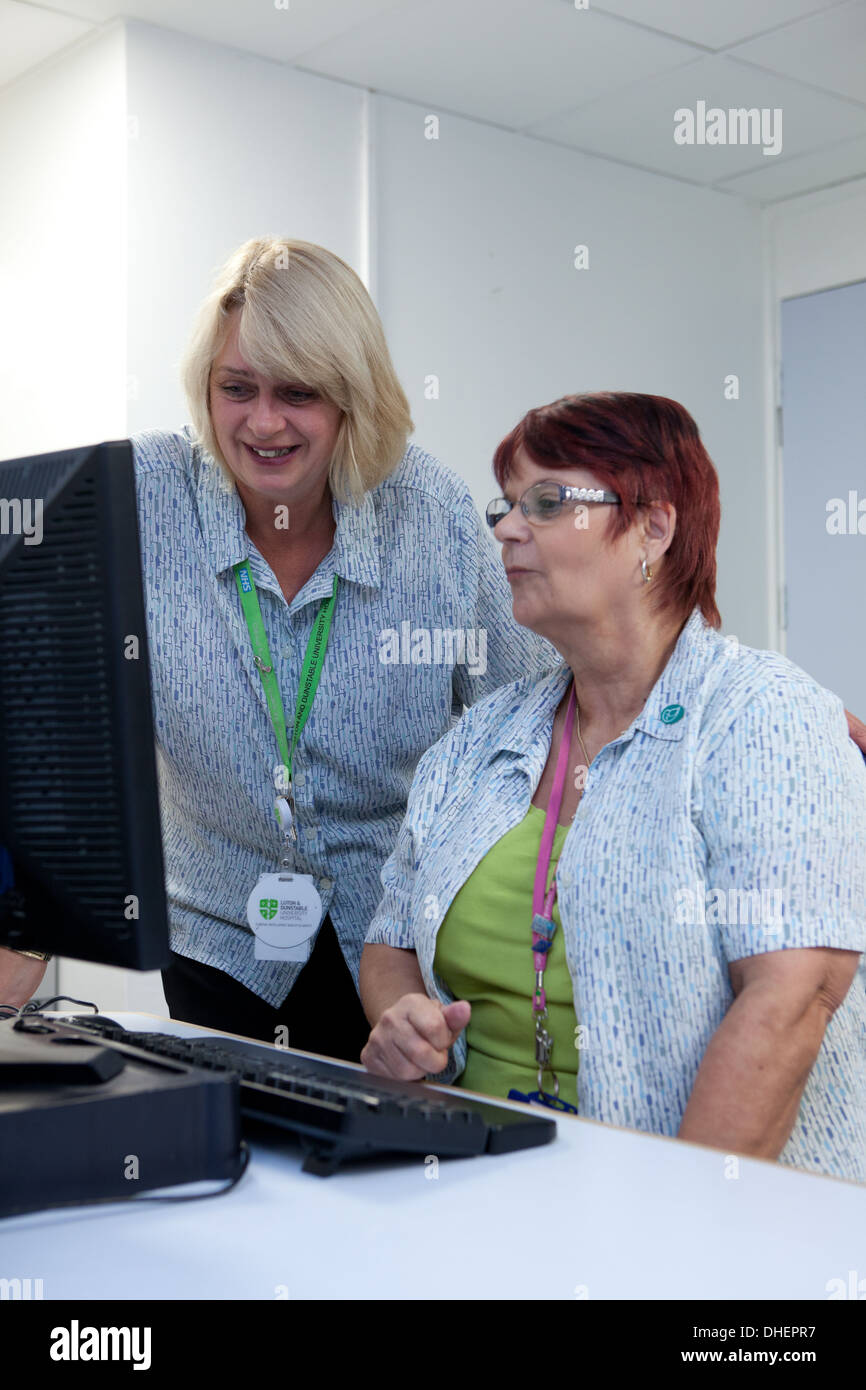 Hospital receptionists check appointments in an outpatient depatment UK Stock Photo