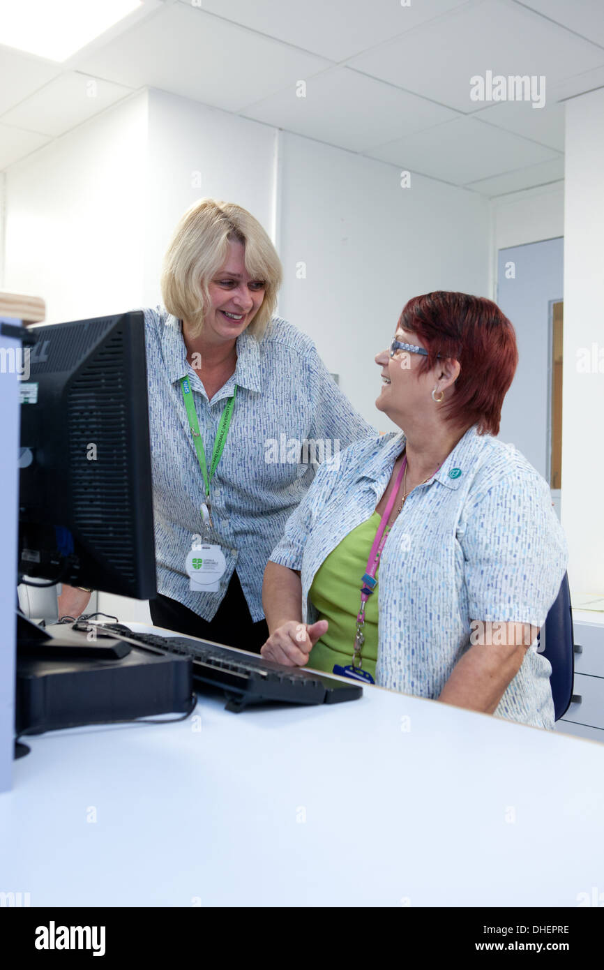 Hospital receptionists check appointments in an outpatient depatment UK - Stock Image
