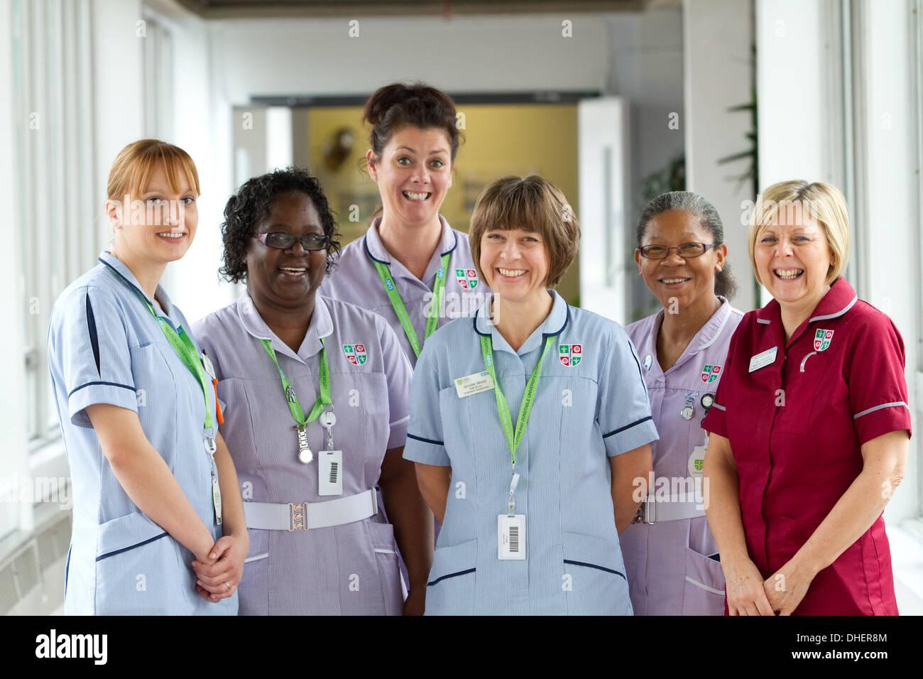 A group of 5 nurses smile toward the camera in a hospital corridor UK - Stock Image