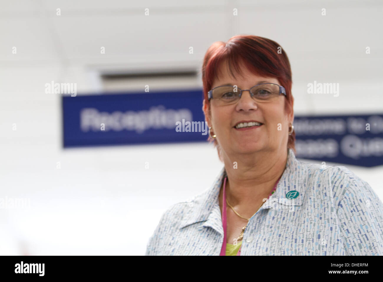A welcoming hospital receptionist smiles to camera UK - Stock Image