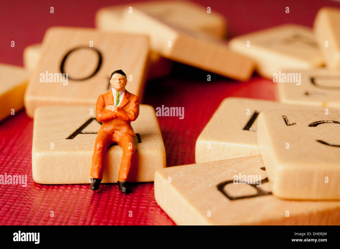 man figurine sitting on scrabble letter - Stock Image