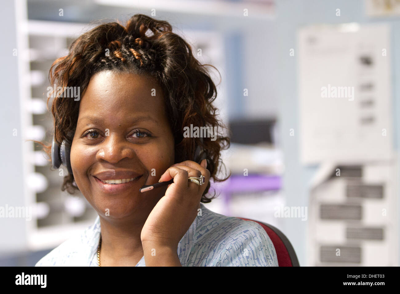 A hospital receptionist takes a call UK - Stock Image