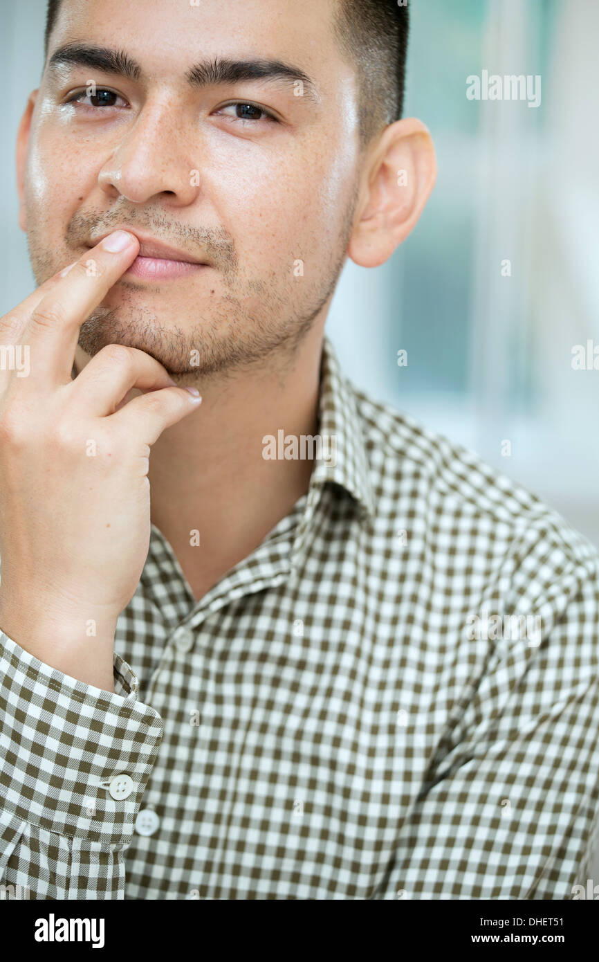 Mid adult man touching his lip - Stock Image