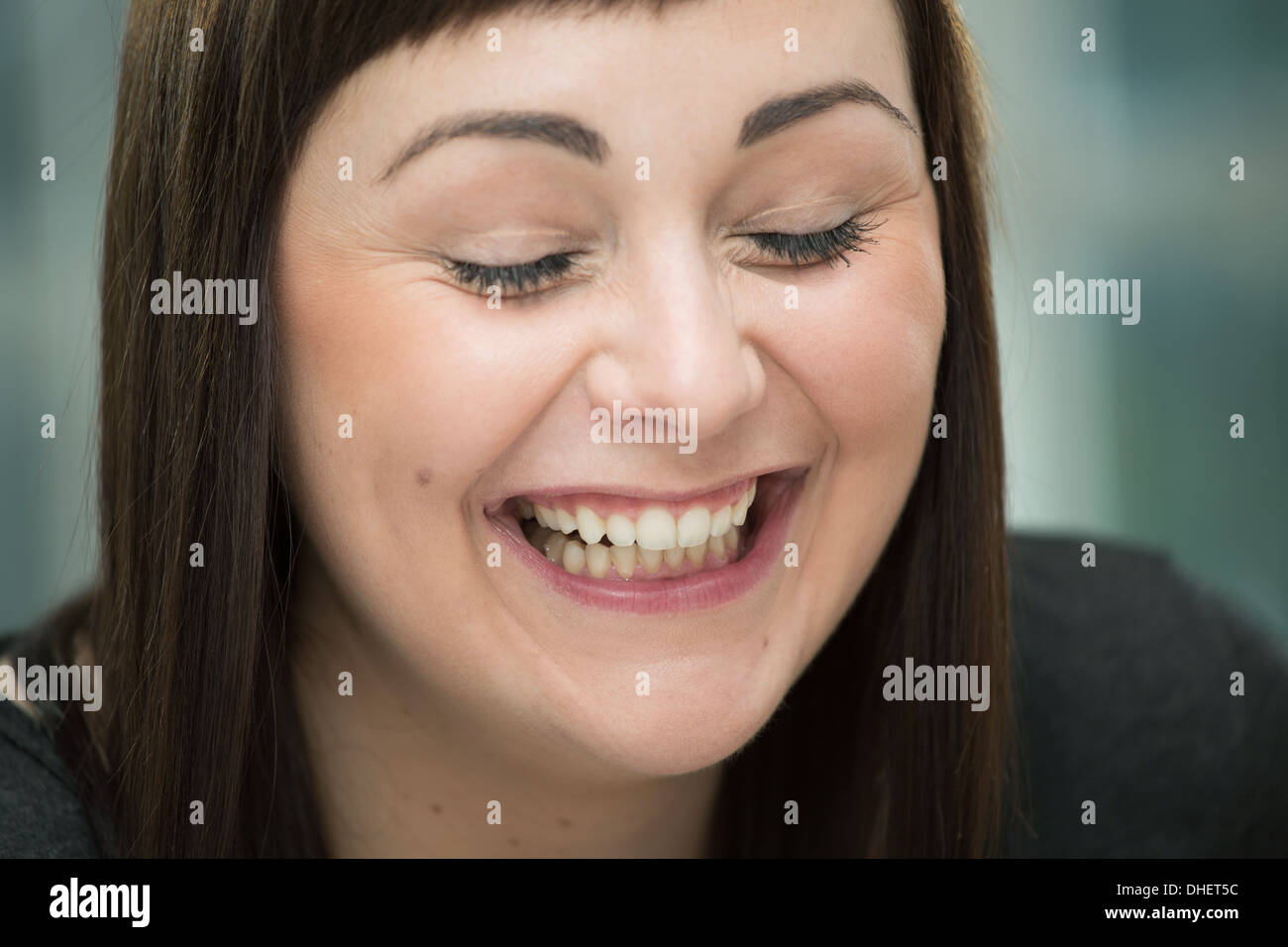Young woman laughing, eyes closed - Stock Image