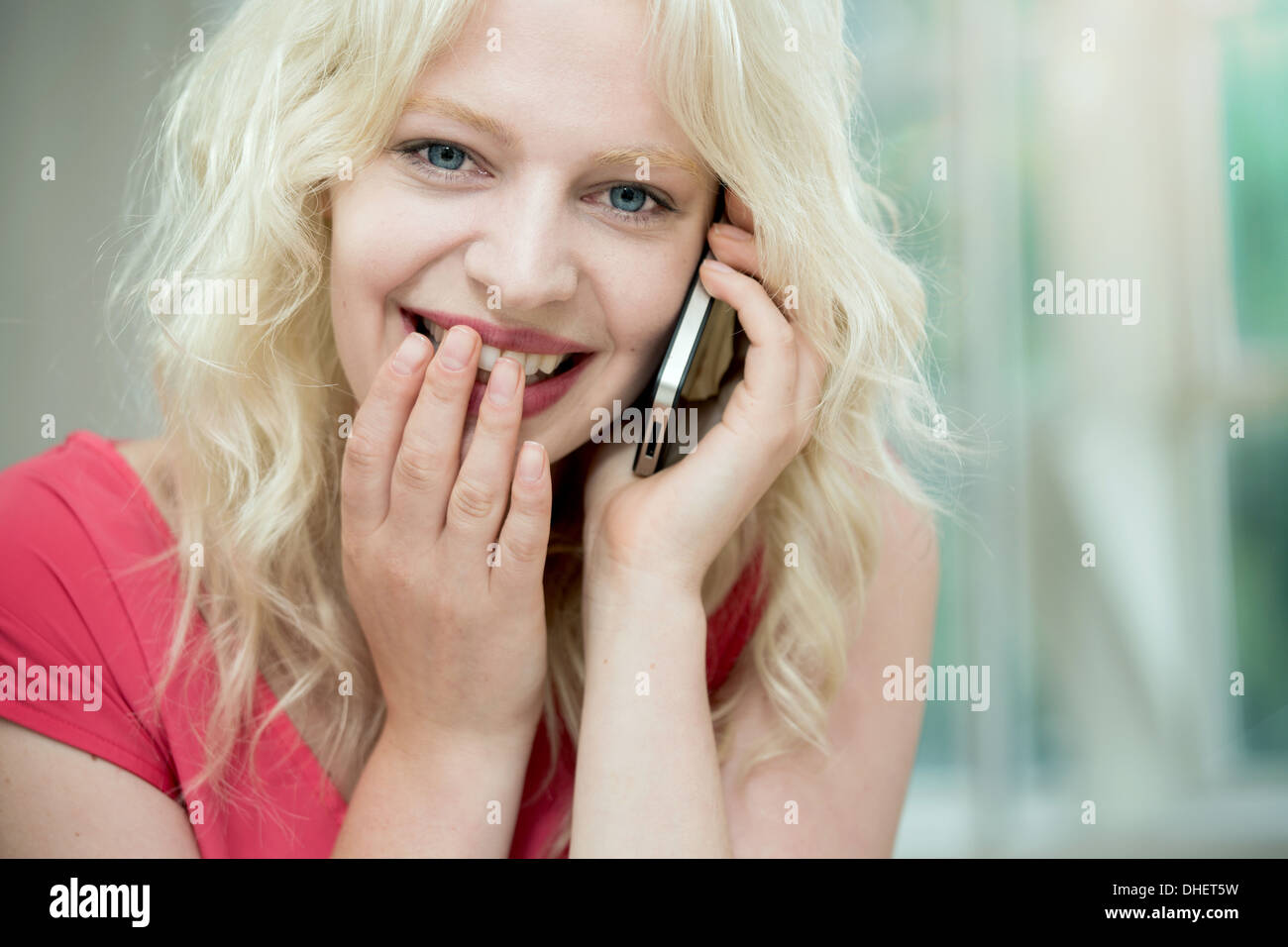Young woman on cellphone, giggling - Stock Image