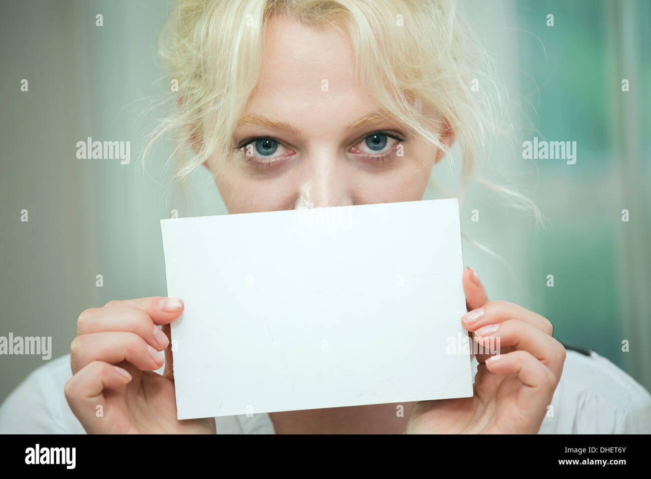 Young woman holding a blank card over her face - Stock Image