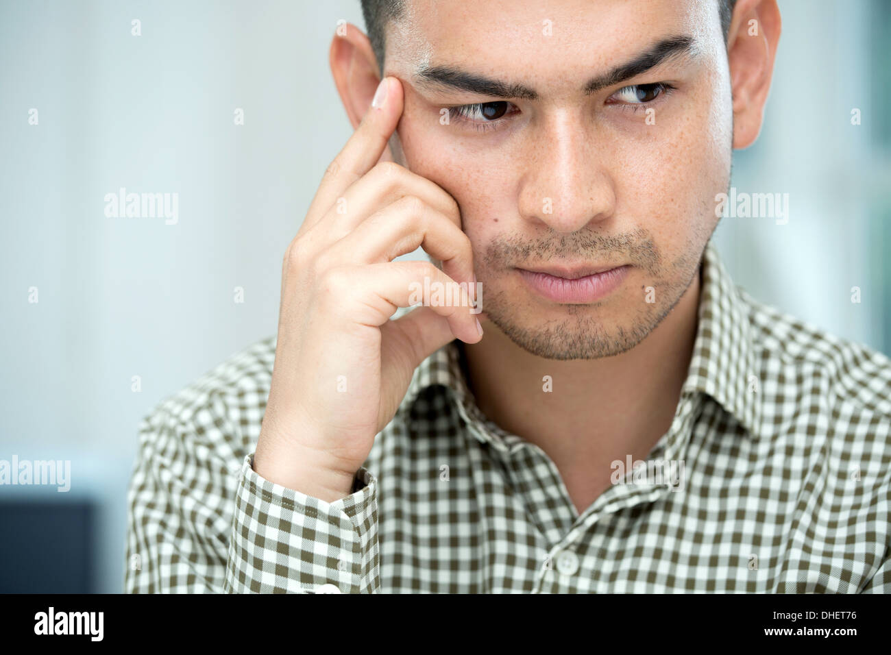 Mid adult man deep in thought - Stock Image