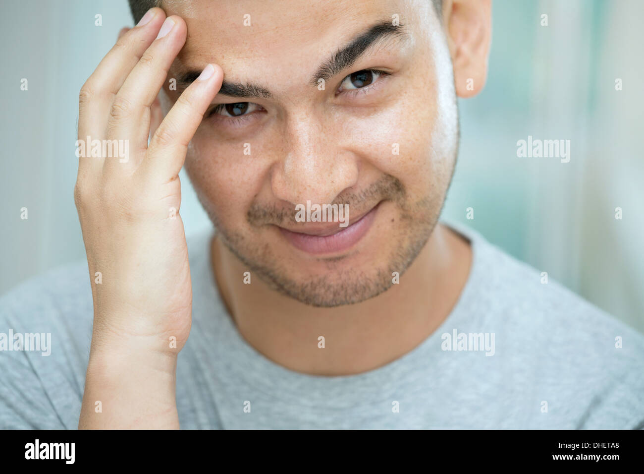 Mid adult man touching his face - Stock Image