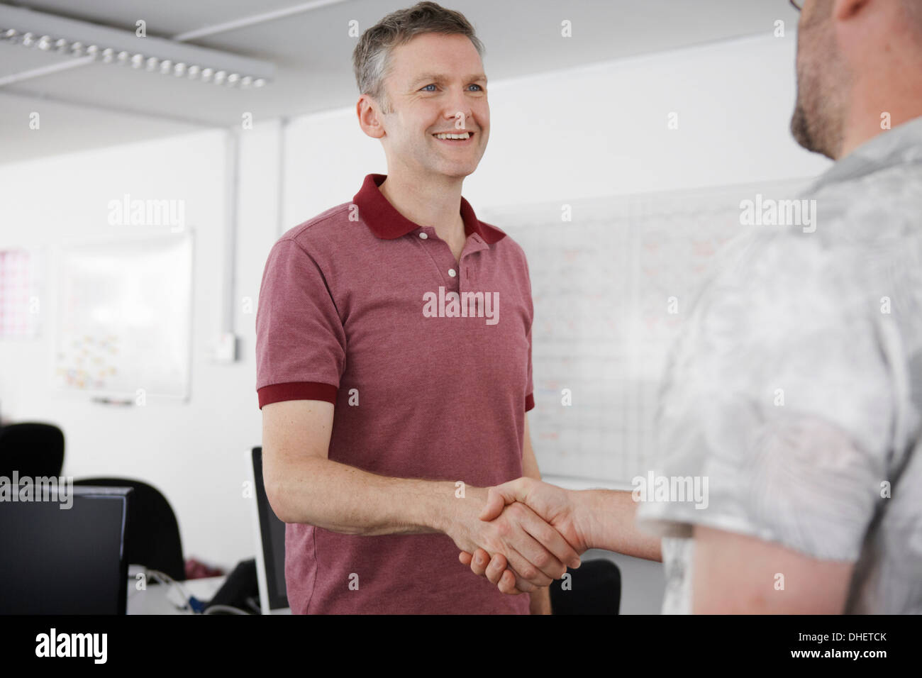 Men shaking hands in office - Stock Image