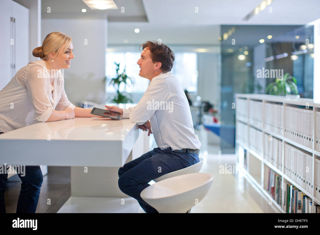 Businesspeople chatting in office - Stock Image