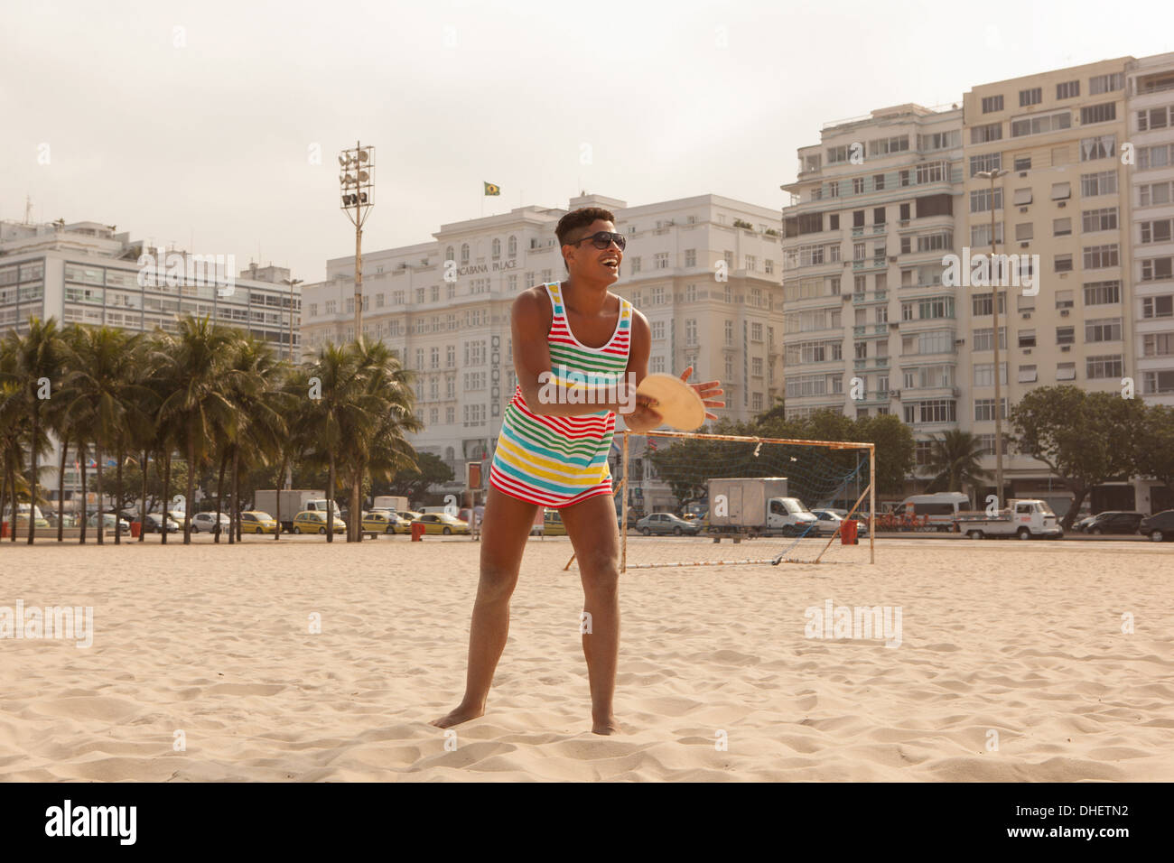 Young man about to hit ball with bat on Copacabana Beach, Rio de Janeiro, Brazil - Stock Image